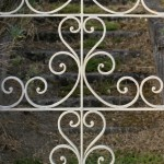wrought_iron_gate_-_decorative_gate_opens_on_stone_stairs_leading_to_an_abandoned_french_seaside_villa_